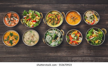 Vegan or vegetarian restaurant dishes top view, hot spicy indian soups, rice and salads in copper bowls. Traditional indian cuisine meal assortment on wood background. Healthy eastern local food
