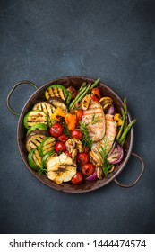 Vegan, vegetarian, seasonal, summer eating concept. Grilled vegetables and chicken breast in a pan on a dark black table. Top view flat lay copy space background