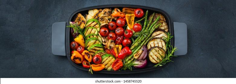 Vegan, vegetarian, seasonal, summer eating concept. Grilled vegetables in a pan on a dark black table. Top view flat lay background