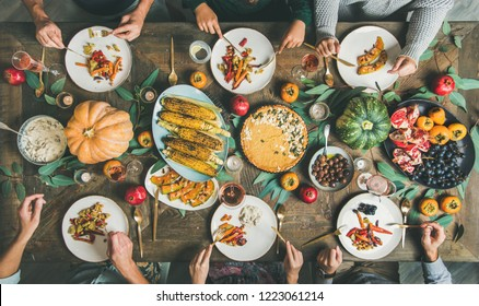 Vegan or vegetarian Thanksgiving, Friendsgiving holiday celebration. Flat-lay of friends eating meals at Thanksgiving Day table with pumpkin pie, roasted vegetables, fruit, rose wine, top view