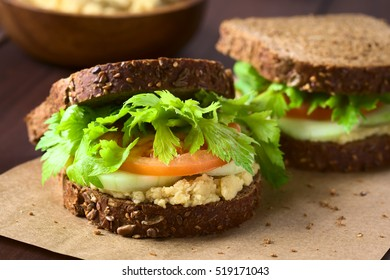 Vegan wholegrain sandwich with celery leaves, tomato, cucumber and chickpea spread or hummus, photographed with natural light (Selective Focus, Focus on the front of the sandwich)