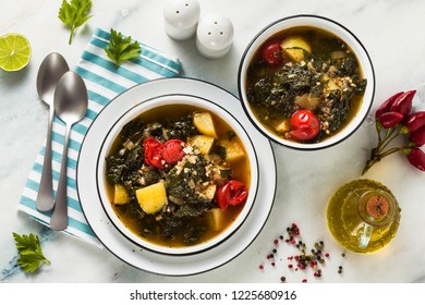 vegan winter kale soup with buckwheat , cherry tomatoes and potatoes. tasty full vegetable food for the whole family