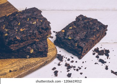 Vegan zucchini flourless paleo brownies and pumpkin brownies (keto, low carb and gluten-free) on a wooden background. Close up