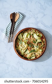 A vegan zucchini noodle salad with fresh zucchini in ribbons tossed with Thai peanut dressing and topped with salted roasted peanuts and fresh basil in a wooden bowl.