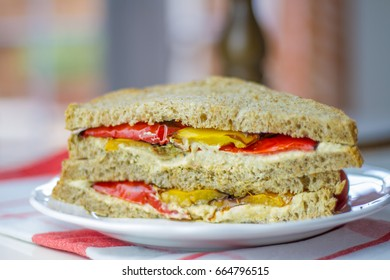A vegan/vegetarian sandwich for lunch of homemade whole wheat bread with houmou (hummus) and roasted peppers on a table for lunch with patio doors in the background.  Messy rustic style.