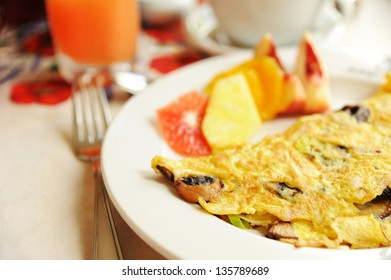 Vegatable omelet served with fruits and grapefruit juice