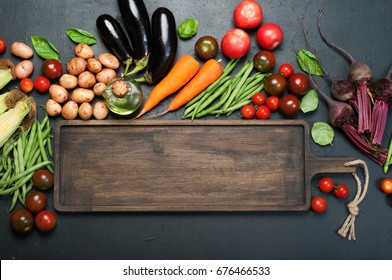 Vegetable background. A long brown wooden board, next to which lie fresh juicy organic vegetables, such as eggplants, carrots, tomatoes, asparagus beans, potatoes, beets etc, against a dark background