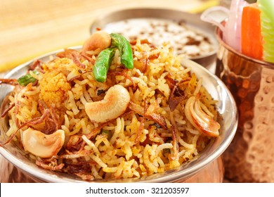 Vegetable Biriyani, Indian cuisine accompanied with fresh slice of carrot, cucumber, onion and Raita garnished with fried beans,onion and cashew nuts