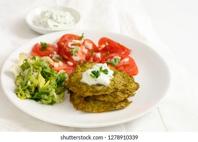 vegetable broccoli pancakes with yoghurt dip, lettuce and tomato, healthy slimming food, white plate on a white table, selected focus, narrow depth of field