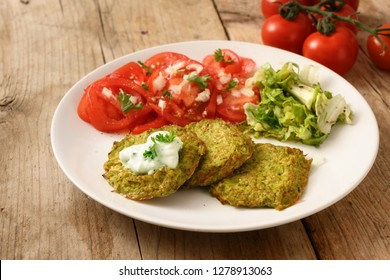 vegetable broccoli pancakes with yoghurt dip, lettuce and tomato, healthy slimming food, white plate on a rustic wooden table, selected focus, narrow depth of field