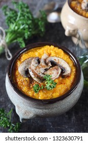 Vegetable carrot soup with mushroom and parsley dressing in two ceramic tureen. Rustic style