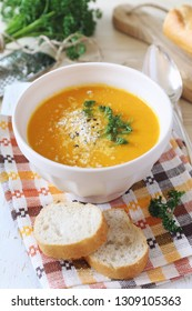 Vegetable carrot soup with parsley, grated cheese and baguette