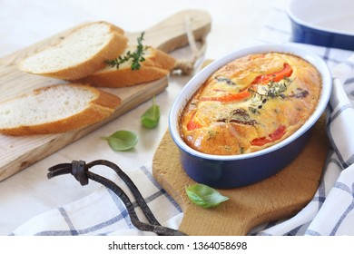 Vegetable Clafoutis with red bell pepper and and dried tomatoes in ceramic bakeware
