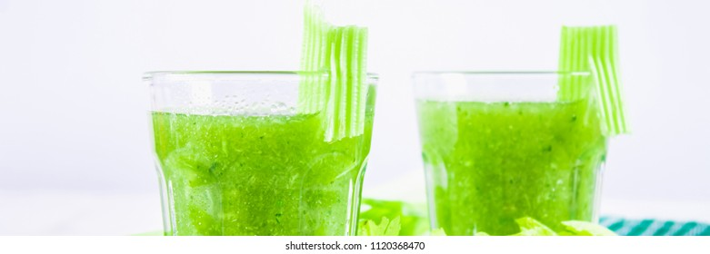 Vegetable cocktail made from celery leaves, healthy lifestyle on a white wooden background.