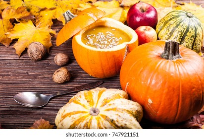 Vegetable cream soup in a pumpkin on a wooden table