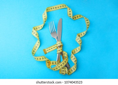 Vegetable diet for weight loss. Fork and knife are wrapped in  yellow measuring tape on blue background