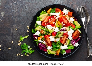 Vegetable dish, salad with avocado, pepper, tomato, italian mix, fresh lettuce, feta cheese and pine nuts. Healthy food. Top view