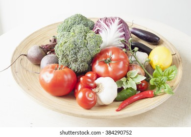 Vegetable display with tomatoes, broccoli, aubergine, beetroot, lettuce and garlic