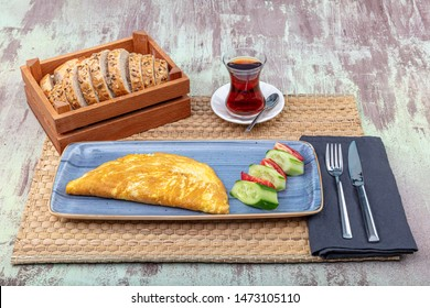 Vegetable egg omelet on a white plate ,Vegetarian omelet with fried tomatoes ,fresh sliced spring onions and spices on a burlap and on old wood background. Breakfast recipe