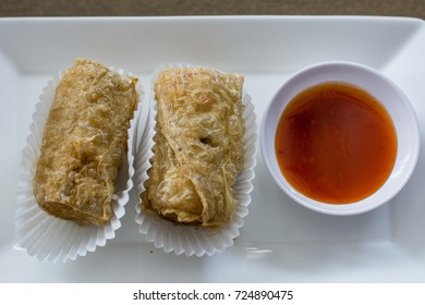 Vegetable fried spring rolls served with bittersweet sauce on white dish. close up.