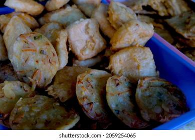 vegetable fritter or gorengan or bakwan or bala-bala from Indonesian cuisine on tray. Street food