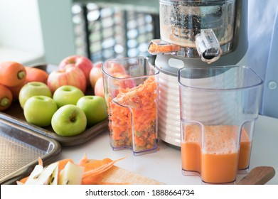 Vegetable and fruit juice healthy with food juicer machine.Woman juicing green and red apple fruits as part of her wellness food or detox smoothie.Cold pressed juice.
