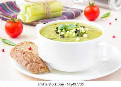 Vegetable green healthy cream soup with avocado, celery, zucchini and herbs in a white cup as an appetizer