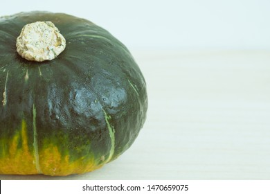 "Vegetable / ingredients concept : Green pumpkin ""坊ちゃんかぼちゃ""on wooden table background. Translation:""坊ちゃんかぼちゃ"" is a Name of this Pumpkin in Japanese."