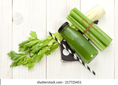 Vegetable juice in bottle with celery stalk on white wood background flat lay