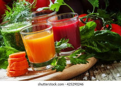 Vegetable juice in glasses, set of colored drinks, vintage wooden background, selective focus