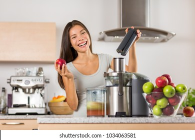 Vegetable juice healthy food juicer machine- Asian woman juicing green and red apple fruits as part of her wellness food, detox smoothie. Beautiful happy mixed Asian woman with juice maker in kitchen.