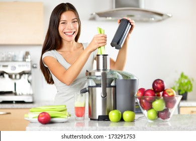 Vegetable juice raw food - healthy eating woman with juicer juicing green vegetables and apple fruits as part of her wellness food. Beautiful happy mixed Asian woman with juice maker in kitchen.