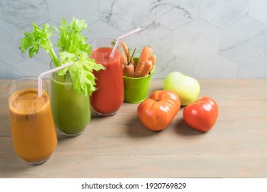Vegetable juices of carrot, celery and tomato on a wooden background in tall glass glasses.