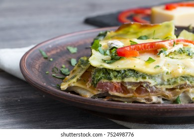 Vegetable lasagne on ceramic plate - italian cuisine - vegetarian diet. Extreme closeup.