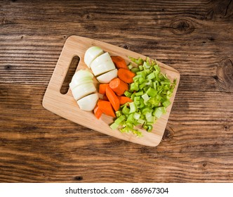 Vegetable mirepoix of carrots, celery and onions  on a cutting board