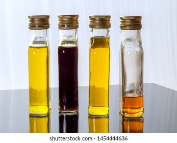 Vegetable oil in glass transparent bottles with screw caps. Bottles of vegetable oil reflected on the dark surface.