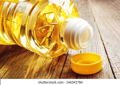 Vegetable oil in plastic bottle closeup on the old wooden table