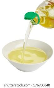 Vegetable oil runs from plastic bottle in a white bowl, white background