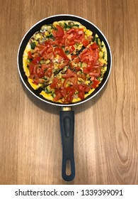 Vegetable omelette in frying pan on wooden surface, made with tomatoes, courgettes, onions and, of course, eggs.