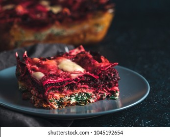 Vegetable Packed Rainbow lasagne on dark background.Ideas and recipes for healthy vegetarian dinner or lunch.Lasagne with beetroot, pumpkin, mushrooms, ricotta, spinach, mozarella. Copy space for text