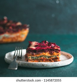 Vegetable Packed Rainbow lasagne on green background.Ideas and recipes for healthy vegetarian dinner or lunch.Lasagne with beetroot, pumpkin, mushrooms, ricotta, spinach, mozarella.Copy space for text
