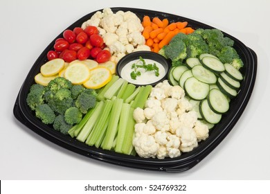 Vegetable party platter with cucumbers, broccoli, squash, cherry tomatoes, cauliflower, and baby carrots served on a black plate and shot on white background.