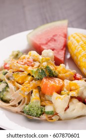 Vegetable Primavera with white sauce and shredded cheese with corn on the cob and slice of watermelon