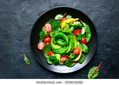 Vegetable salad with avocado, cucumber, cherry tomato, chard leaves and broccoli on a black plate over dark slate, stone or concrete background .Top view with copy space.