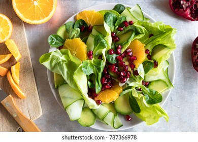 Vegetable salad with avocado, orange and pomegranate on a bright metal background, top view.