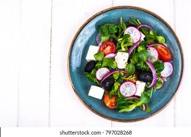 Vegetable salad with black olives and feta. Studio photo