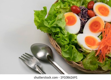 Vegetable salad and boiled eggs in a wicker tray and utensils, isolated on white background.