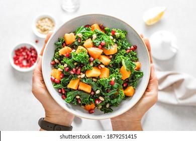 Boule de salade de légumes dans les mains des femmes. Salade de kale fraîche et de citrouille cuite. Concept d'alimentation saine