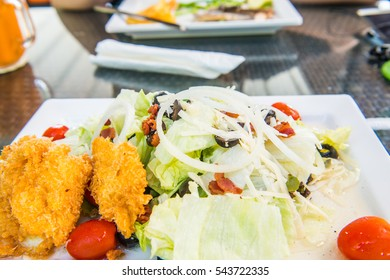 Vegetable salad with breaded fried fish, Thailand.