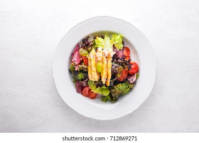 Vegetable salad with chicken and mango sauce on a wooden background. Top view. Free space for text.